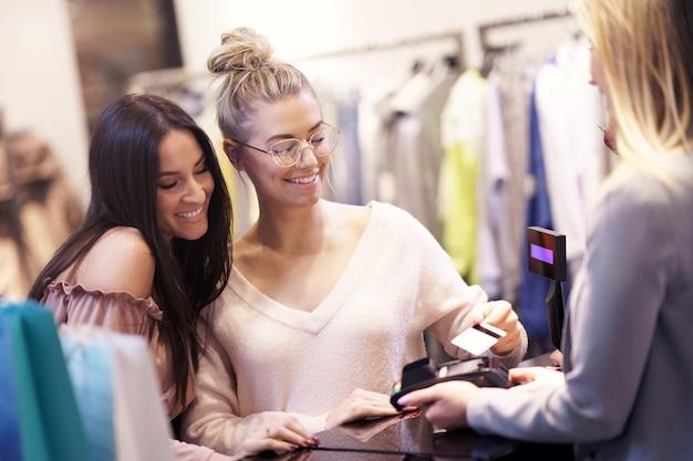 Groupe d'amis heureux achetant des vêtements dans un centre commercial
