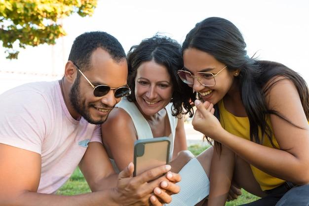 Groupe d'amis heureux à l'aide de smartphone