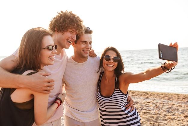 Groupe d'amis heureux aimant les couples en plein air sur la plage, prendre un selfie par téléphone mobile