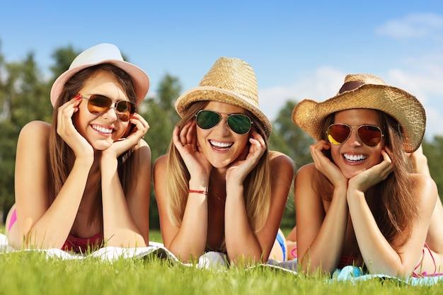 Groupe d'amis heureux allongé sur l'herbe et bronzer