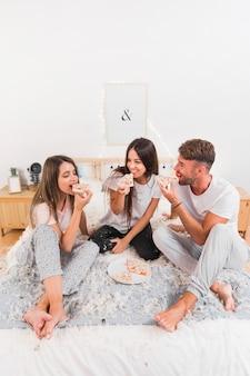 Groupe d'amis heureux assis sur le lit en mangeant des pizzas