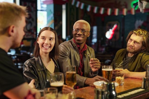 Groupe d'amis heureux assis à la table buvant de la bière et se parlant tout en se reposant dans le pub