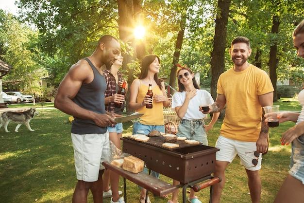 Groupe D'amis Heureux Ayant De La Bière Et Un Barbecue En Journée Ensoleillée. Repos Ensemble En Plein Air Dans Une Clairière Ou Une Cour Photo gratuit