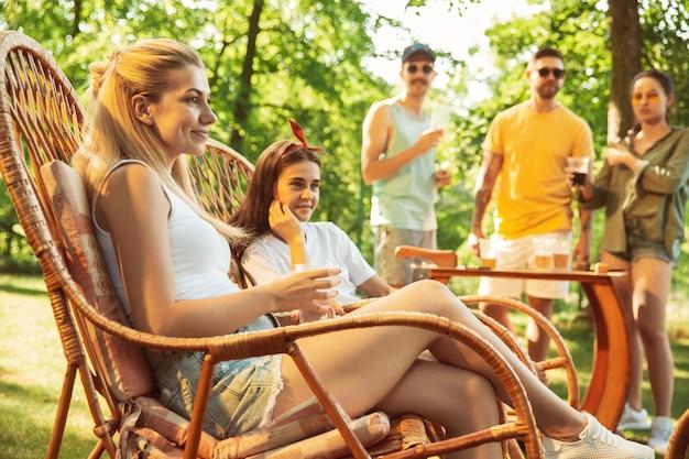 Groupe d'amis heureux ayant de la bière et un barbecue en journée ensoleillée. repos ensemble en plein air dans une clairière ou une cour
