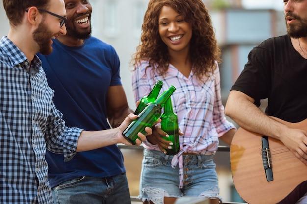Groupe d'amis heureux ayant une fête de la bière en été se reposant ensemble en plein air célébrant et