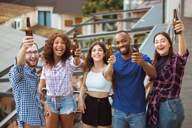 Groupe d'amis heureux ayant une fête de la bière en journée ensoleillée.