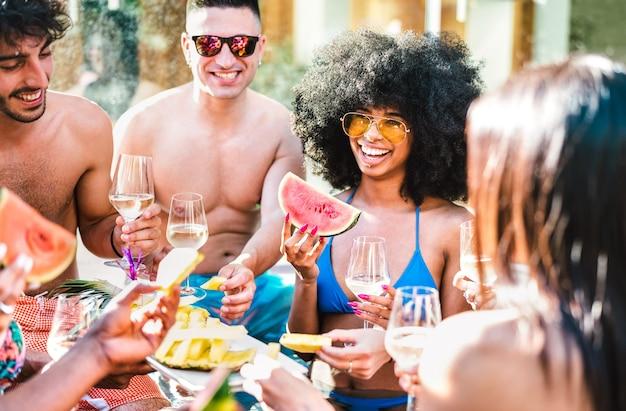 Groupe d'amis heureux buvant du champagne au vin blanc à la fête au bord de la piscine