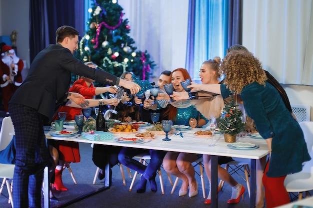 Groupe d'amis heureux célébrant noël ou le nouvel an. un homme verse du champagne dans des verres. des femmes rient, assises à une table près du sapin de noël.