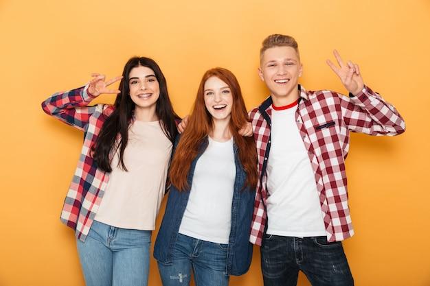 Groupe d'amis heureux de l'école montrant le geste de paix