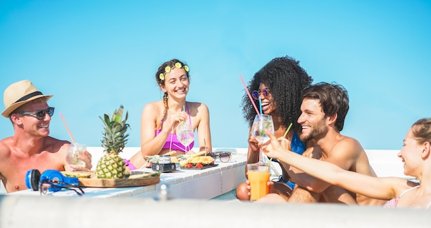 Groupe d'amis heureux faisant une fête d'été en bateau avec des cocktails tropicaux