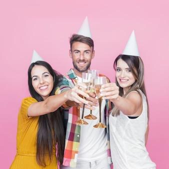 Groupe d'amis heureux grillage verre à vin