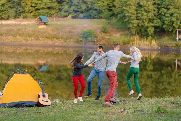 Groupe d'amis heureux avec guitare, s'amuser en plein air, danser et sauter près du lac en arrière-plan du parc le beau ciel. camping amusant