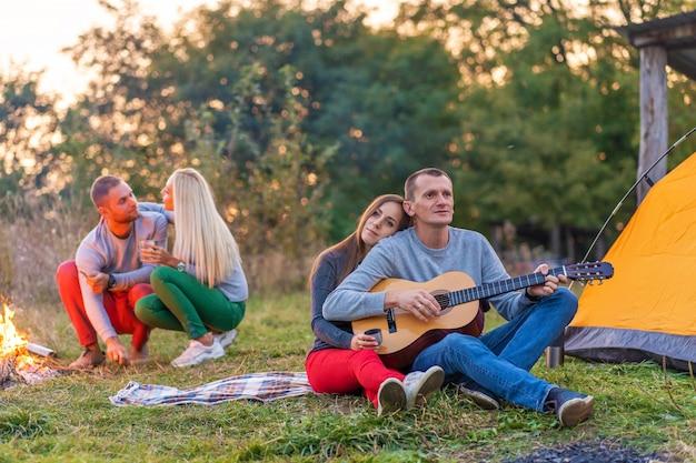Groupe d'amis heureux avec guitare, s'amuser en plein air, près de feu de joie et tente touristique. camping plaisir famille heureuse