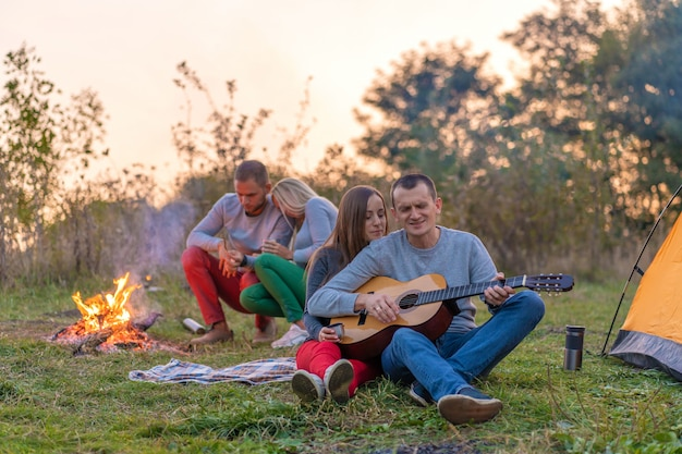 Groupe d'amis heureux avec guitare, s'amuser en plein air, près de feu de joie et tente touristique