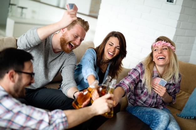 Groupe d'amis heureux jouant aux cartes et buvant