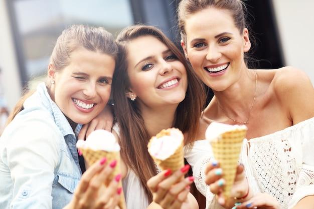 Groupe d'amis heureux mangeant des glaces à l'extérieur