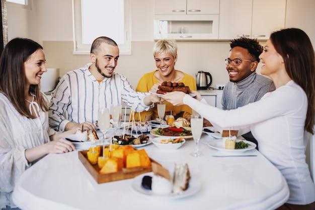 Groupe d'amis heureux multiculturels assis à table à manger et déjeuner à la maison. femme tenant une assiette avec des rouleaux de viande et passant à un mec.
