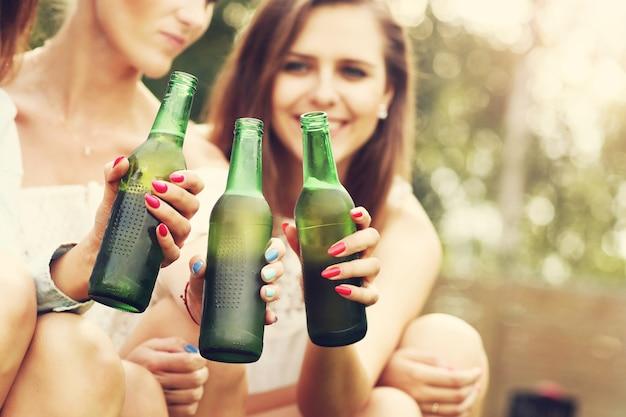 Groupe d'amis heureux prenant une bière à l'extérieur