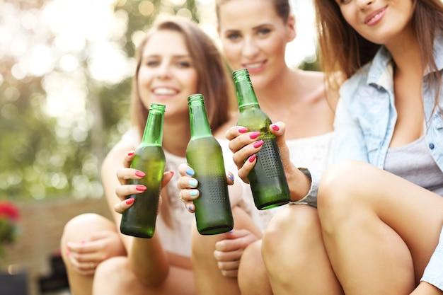 Groupe d'amis heureux prenant une bière en plein air