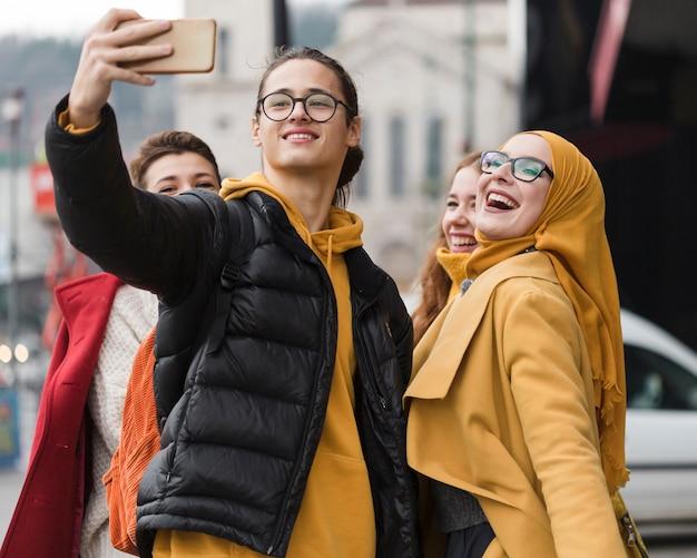 Groupe d'amis heureux prenant un selfie ensemble
