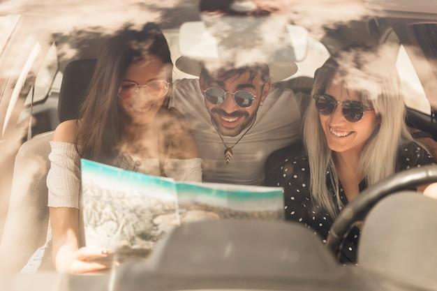 Groupe d'amis heureux en regardant la carte assis à l'intérieur de la voiture