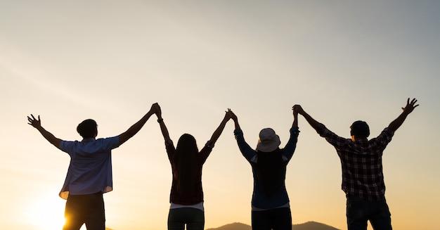 Un groupe d'amis heureux s'amuse avec les bras levés ensemble devant la montagne