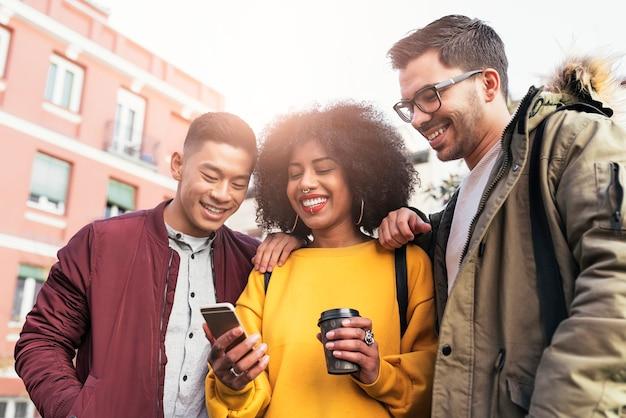 Groupe d'amis heureux utilisant le mobile dans la rue. notion d'amitié.