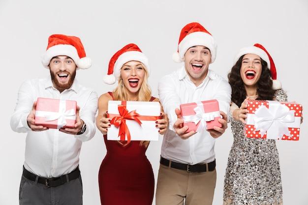 Groupe d'amis heureux vêtus de chapeaux rouges debout isolé sur blanc, célébrant le nouvel an, tenant des boîtes présentes