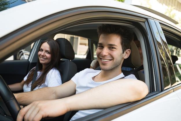 Groupe d'amis heureux sur une voiture blanche