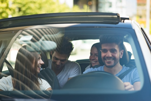 Groupe d'amis heureux sur une voiture