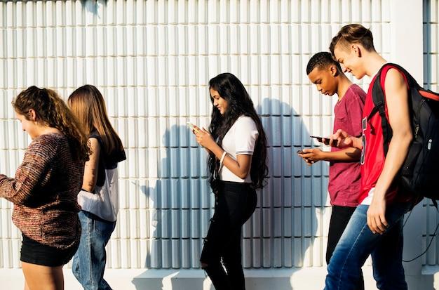 Groupe d'amis jeunes adolescents marchant à la maison après l'école à l'aide de smartphones