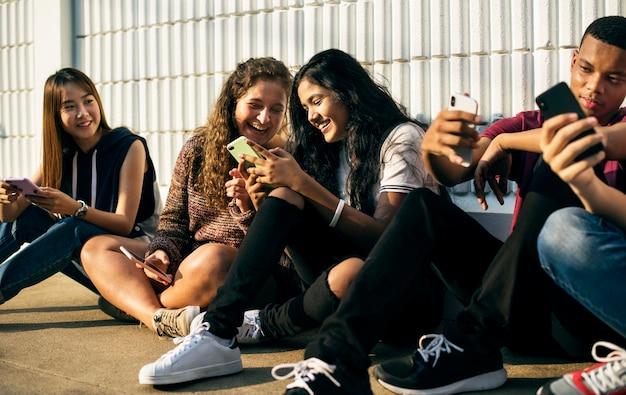 Groupe d'amis jeunes adolescents se détendre ensemble à l'aide de smartphone s