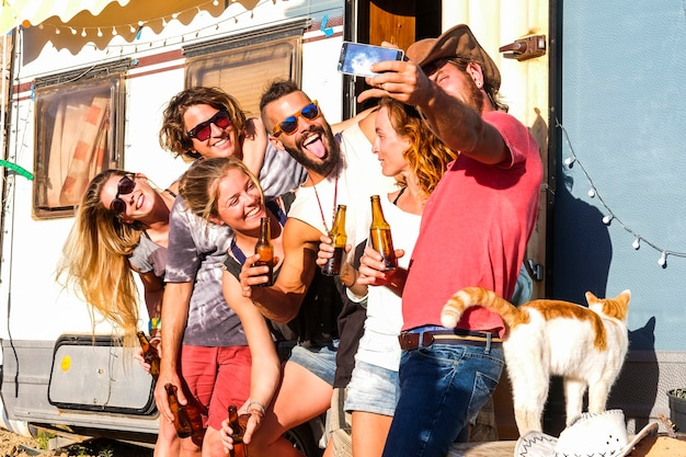 Un groupe d'amis de jeunes prend une photo de selfie dans un mode de vie de vacances à la campagne et un vieux camping-car