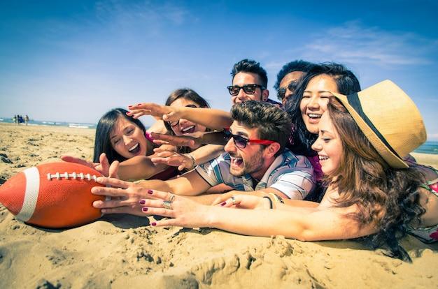 Groupe d'amis jouant avec le ballon de rugby essayant de le retirer du support