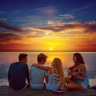 Groupe d'amis jouant de la guitare dans la jetée du coucher du soleil au crépuscule