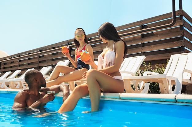 Groupe d'amis jouant et se détendre dans une piscine pendant les vacances d'été