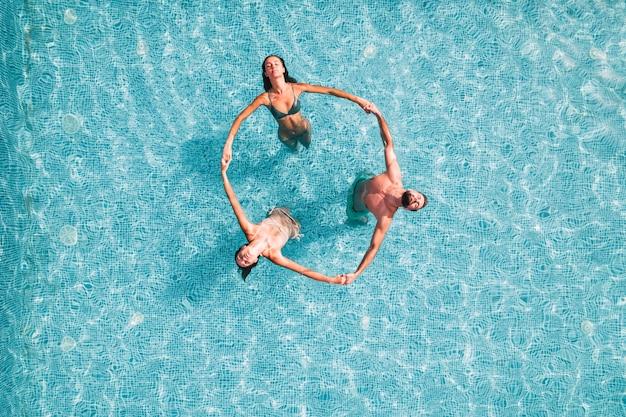 Groupe d'amis jouent ensemble dans une piscine