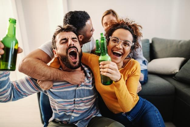 Groupe d'amis joyeux assis à la maison et regardant un match de football à la télévision. leur équipe préférée gagne.