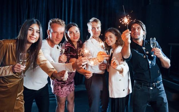 Groupe d'amis joyeux célébrant le nouvel an à l'intérieur avec des boissons à la main.