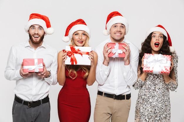 Groupe d'amis joyeux vêtus de chapeaux rouges debout isolé sur blanc, célébrant le nouvel an, tenant des boîtes présentes