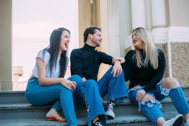 Groupe d'amis latins souriants assis dans la rue de la ville. concept d'été et de personnes.