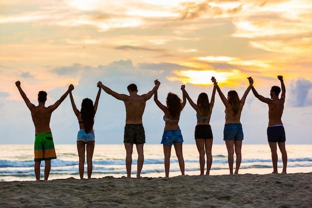 Groupe d'amis en levant les mains sur la plage au coucher du soleil