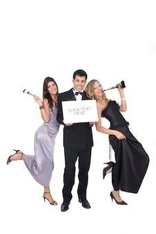 Groupe d'amis lors d'une fête ou à la fête du nouvel an avec signe pour votre texte