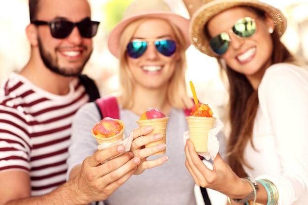 Groupe d'amis mangeant des glaces dans la ville