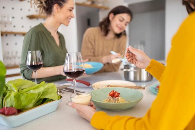 Groupe d'amis, manger des pâtes ensemble dans la cuisine
