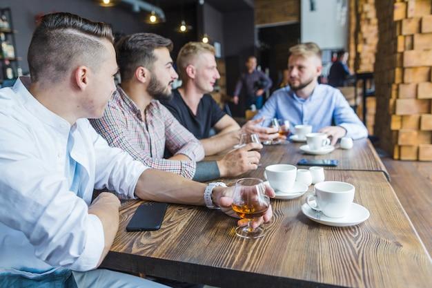 Groupe d'amis masculins appréciant les boissons dans le restaurant