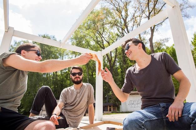 Groupe d'amis masculins partageant une pizza