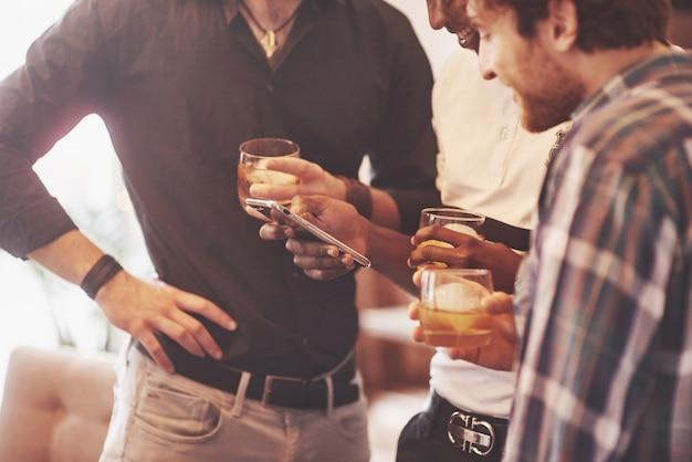 Groupe d'amis mecs avec des verres de whisky
