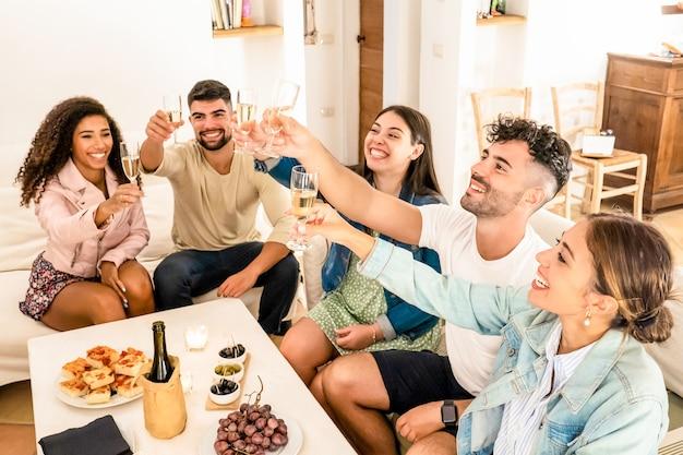 Groupe d'amis métis de grillage avec champagne célébrant à la maison