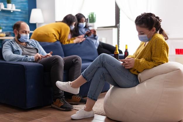 Groupe d'amis métis naviguant sur un smartphone en gardant une distance sociale portant un masque facial pour empêcher la propagation du coronavirus pendant la pandémie mondiale dans le salon avec une bouteille de bière. image conceptuelle
